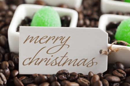 Coffee beans and green candies on a white vessel with Christmas greeting card photo