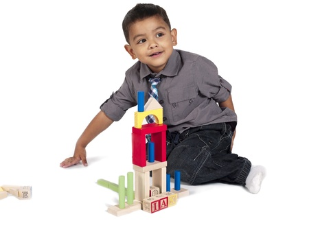Little boy playing toy house blocks on a white background photo