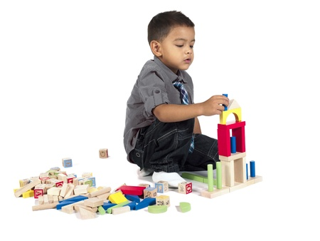 Little boy sitting and playing blocks isolated on photo
