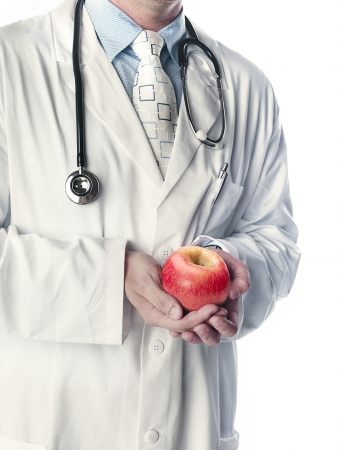 Mid section of a doctor holding apple over white background  Stock Photo - 17285924
