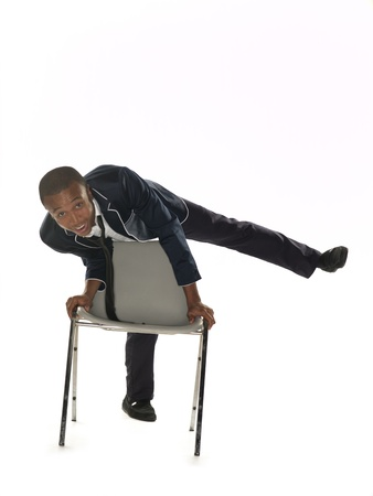 Portrait of a businessman posing on one leg with chair over white background. Model: Nathaniel Stevenson photo