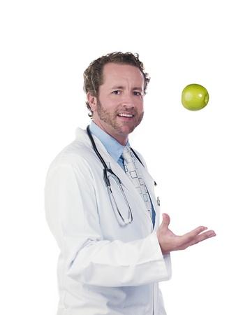 Portrait of a doctor tossing green apple against white background, Model: Derek Gerhardt Stock Photo - 17244691