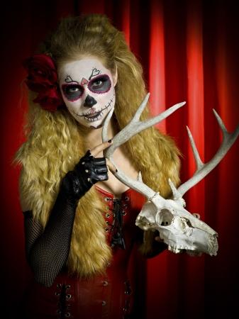 stage makeup: Portrait of a woman in traditional sugar skull holding a animal skull against red background. Model: Christine Vandenberk  MUA: Amanda Wynn - www.awynnemakeup.com and Neelum Saini - www.dmgdesignz.ca Stock Photo