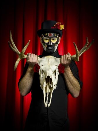 traje mexicano: Retrato de tiro feo hombre con la pintura del cráneo del azúcar presenta con el esqueleto de los animales en la mano. Modelo: Winter Bourne MUA: Amanda Wynn - www.awynnemakeup.com y Neelum Saini - www.dmgdesignz.ca