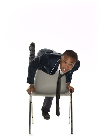 View of a businessman balancing on chair over white background. Model: Nathaniel Stevenson photo