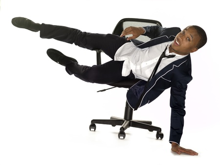 only one teenage boy: View of a businessman falling from chair over white background. Model: Nathaniel Stevenson Stock Photo
