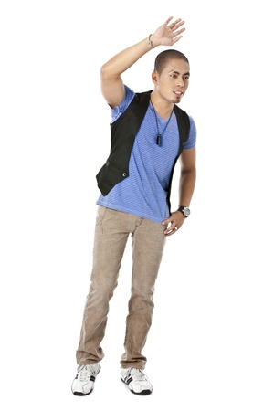 Vertical image of a young man waving at someone isolated in a white background photo