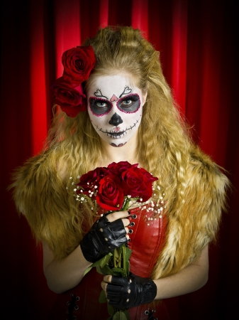 Young woman wearing traditional sugar skull and holding a bouquet of roses. Model: Christine Vandenberk  MUA: Amanda Wynn - www.awynnemakeup.com and Neelum Saini - www.dmgdesignz.ca photo