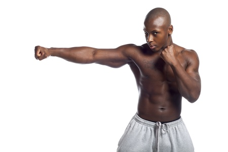 Portrait of a serious African American body builder in boxing stance over white background photo