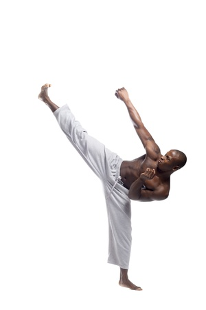combative sport: a young African American man practicing karate over white background Stock Photo