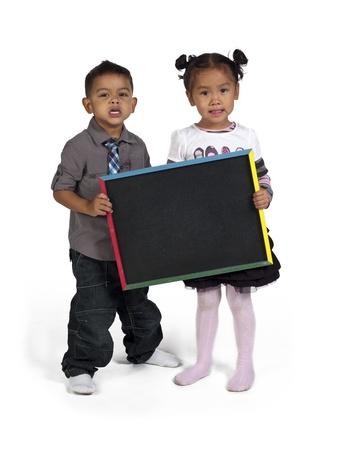 slateboard: Portrait of Asian boy and girl holding slateboard,  and Kai Wall Stock Photo