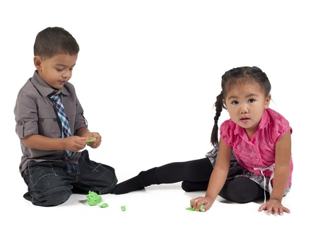 Asian children playing with play dough over white background,  and Kai Wall photo