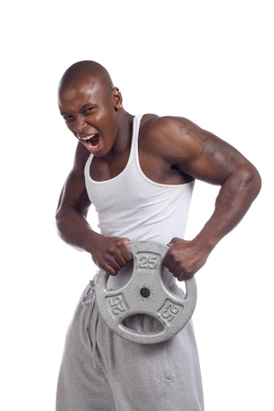 Portrait shot of African-American man holding weight disc and shouting. Model: Gregory Dawson photo