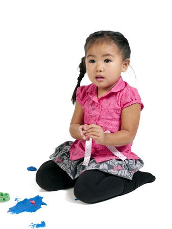 Curious little girl with play dough on white background photo