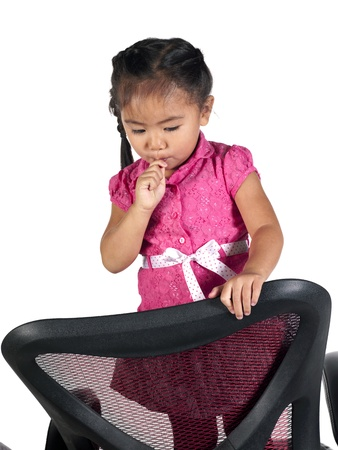 Close-up shot of a cute little girl standing on chair and eating lollipop. Model: Sienna Fulay photo