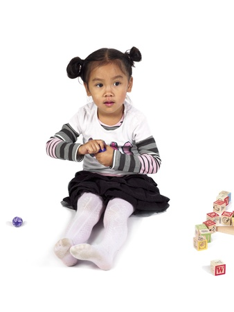 Image of a beautiful little girl playing with toys over white background, Model: Jaedyn Fulay Stock Photo - 17244690