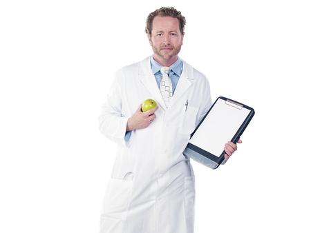 Doctor holding apple and clipboard against white background, Model: Derek Gerhardt Stock Photo - 17244308