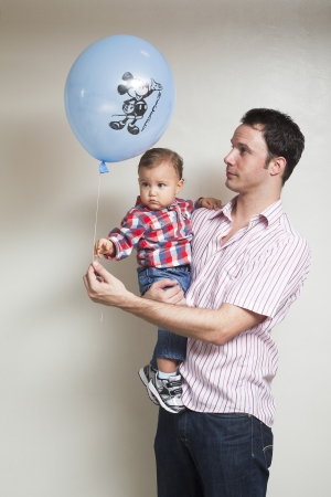 Portrait of father giving a balloon to his son isolated on a background Stock Photo - 17244747