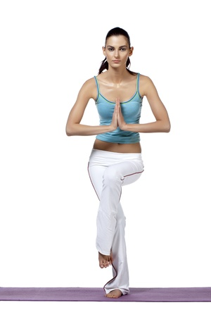 A female fitness instructor demonstrates a standing yoga pose Stock Photo - 17244128