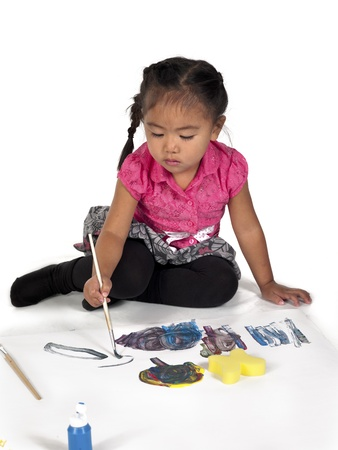 Girl busy painting against white background. photo
