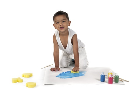 Portrait image of a boy doing painting over plain white background. photo