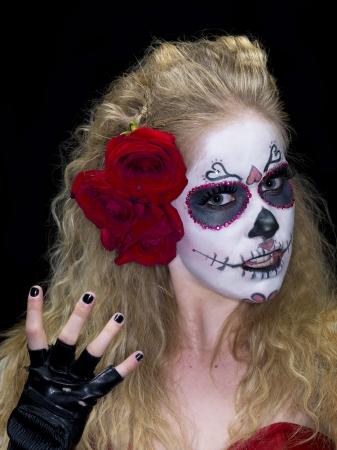 Close-up portrait of a scary woman wearing traditional sugar skull make-up against dark background. Model: Christine Vandenberk photo