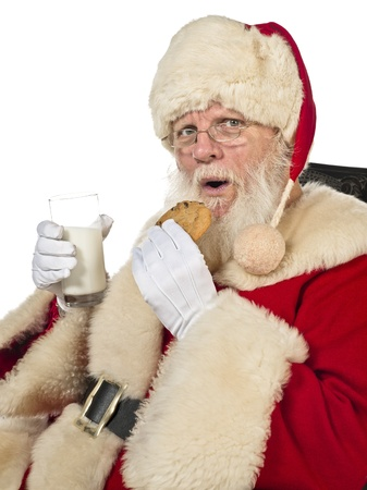 Portrait of santa claus drinking milk and eating cookies photo