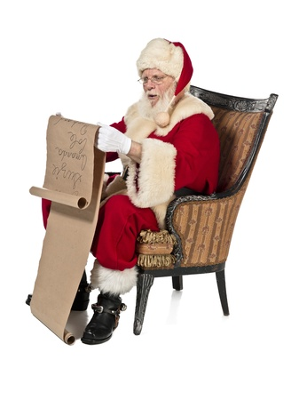 Santa Claus sits on the wooden chair and reading Stock Photo - 17244719