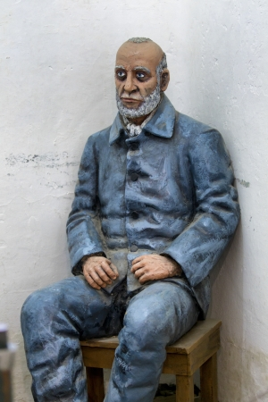 View of a statue of a man sitting on stool.