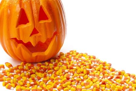 corn kernel: Smiling jack o lantern with candy corn on white background.