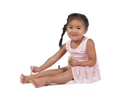 Smiling little Asian girl playing with building blocks over white background, photo