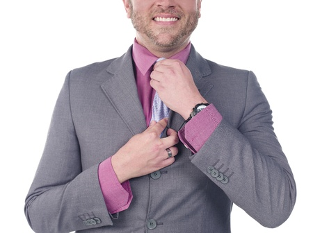 Cropped image of a smiling young doctor adjusting his tie over white background, Model: Derek Gerhardt photo