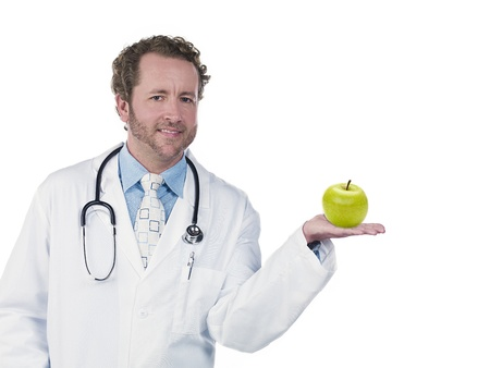 Smiling young doctor displaying green apple over white background, Model: Derek Gerhardt Stock Photo - 17244190