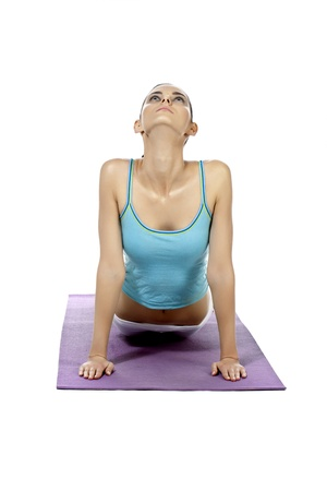 Facade shot of a young female doing yoga exercise in a purple mat isolated in a white background photo