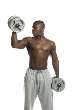 Young man exercising with dumbbell against white background, Model: Gregory Dawson photo