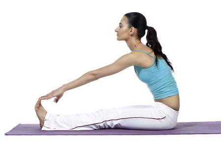 Young woman in a mat reaching her feet as she performs yoga exercise isolated in a white background photo