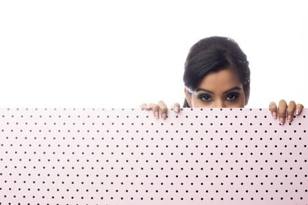 Head shot of an attractive young woman hiding behind a polka dot wall. Model: Sabrina Remkissoon photo
