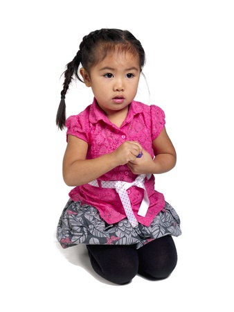 Image of a cute little girl sitting on knees. Model: Sienna Fulay photo