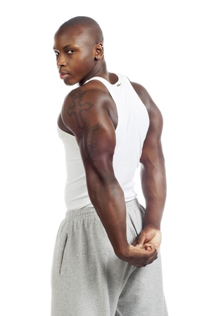 Portrait shot of a black African-American young man flexing triceps muscles against white background. Model: Gregory Dawson photo