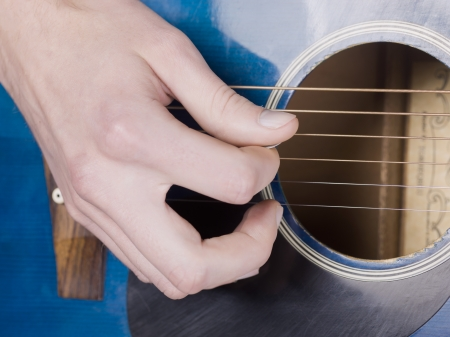 Closed up hand playing an acoustic guitar
