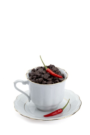 Portrait of a cup with chocolate chips and red chili isolated on a white background photo