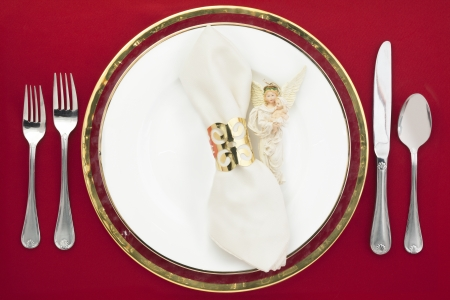 Silverware and plate with white napkin and angel decoration on a red background photo