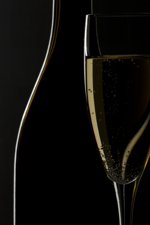Glass of champagne and wine bottle in a dark background Standard-Bild