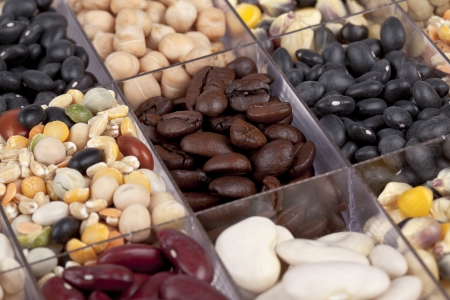 Cropped image of assorted beans divided into a transparent container photo