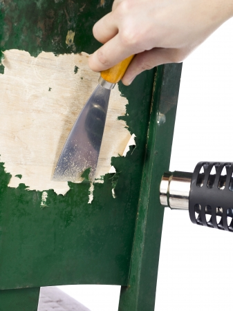 Close-up shot of a human hand holding heat gun and chisel while stripping paint from a old wooden chair.