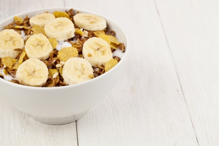 cropped image: Cropped image of a bowl with cereals and a slice banana isolated on a white background