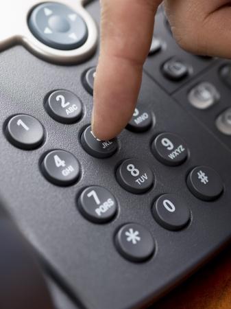 Close-up cropped shot of human finger pressing landline phone numbers.