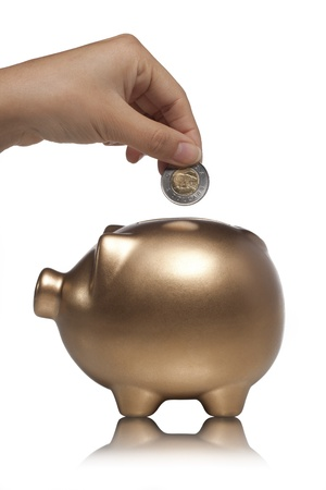 Close-up cropped shot of human hand putting coin in gold piggy bank on white background. Stock Photo - 17251224