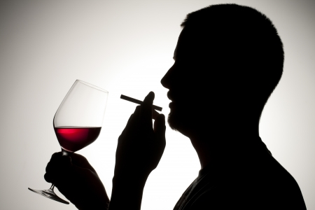 A close-up silhouette of a man smoking and drinking wine isolated