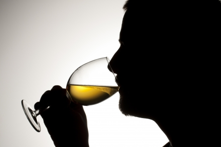 Side view silhouette of a man tasking white wine. photo